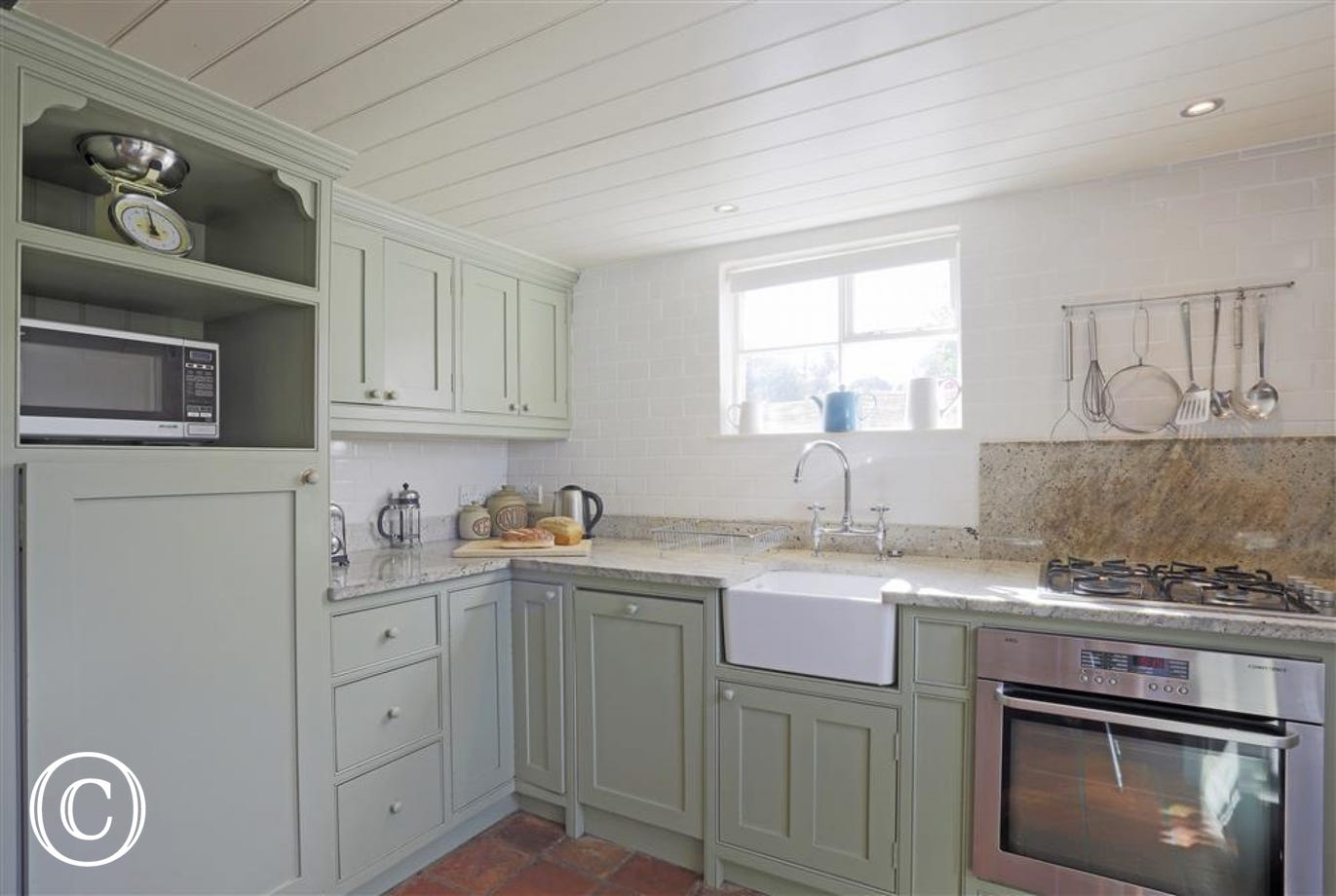 These sage green coloured kitchen units add to the countryside chic feel of the cottage.