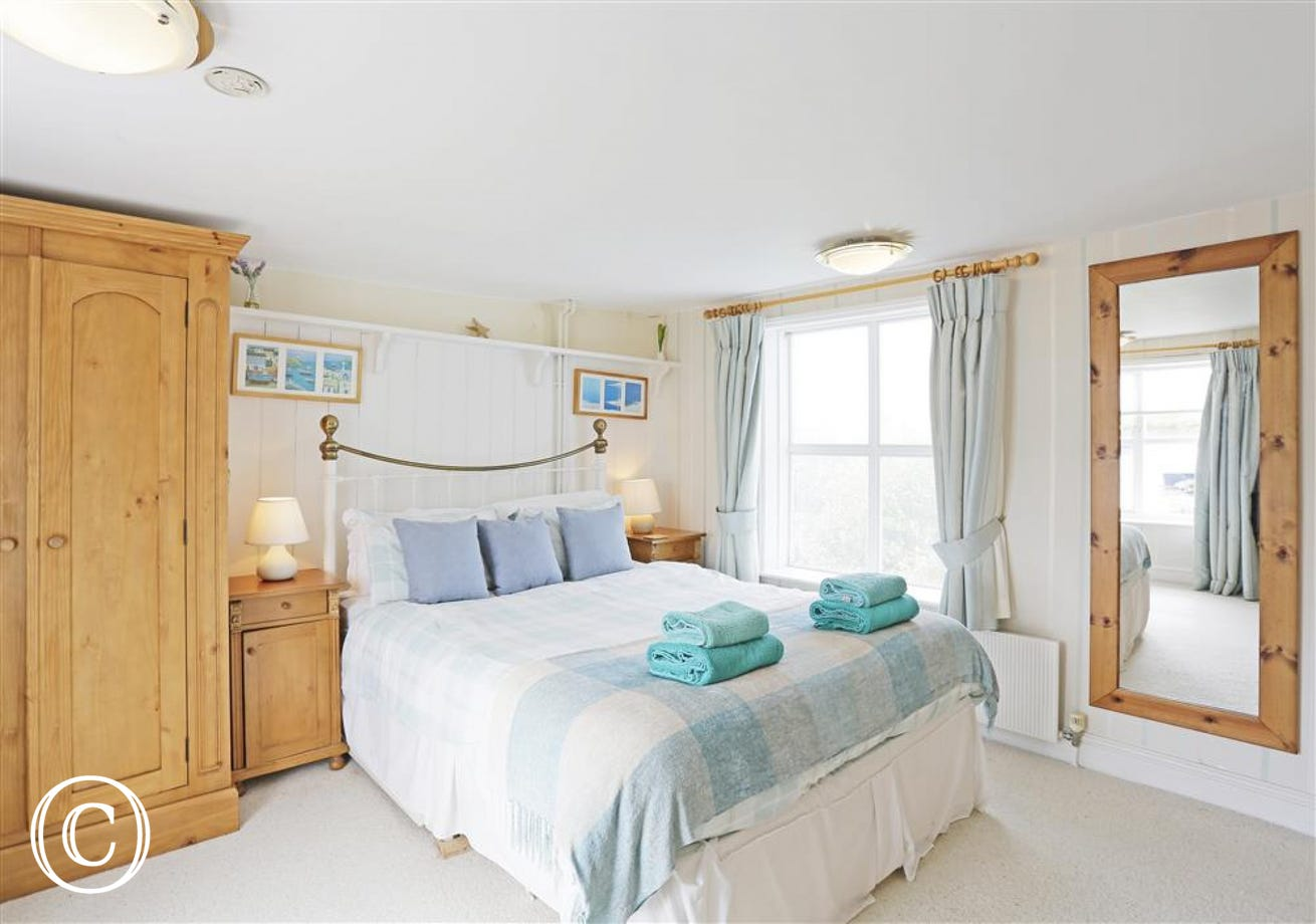 This light airy master bedroom has views over the harbour and a handy en-suite shower.