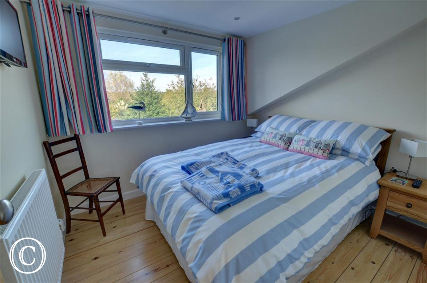 Relax down into this double bed in the main double bedded room with beside tables and view across the rear garden.