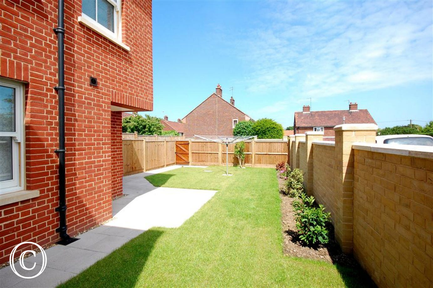 Enjoy this rear courtyard garden with lawn and outside seating.