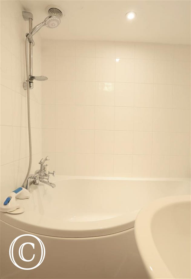 A white bathroom suite with a lovely corner bath.