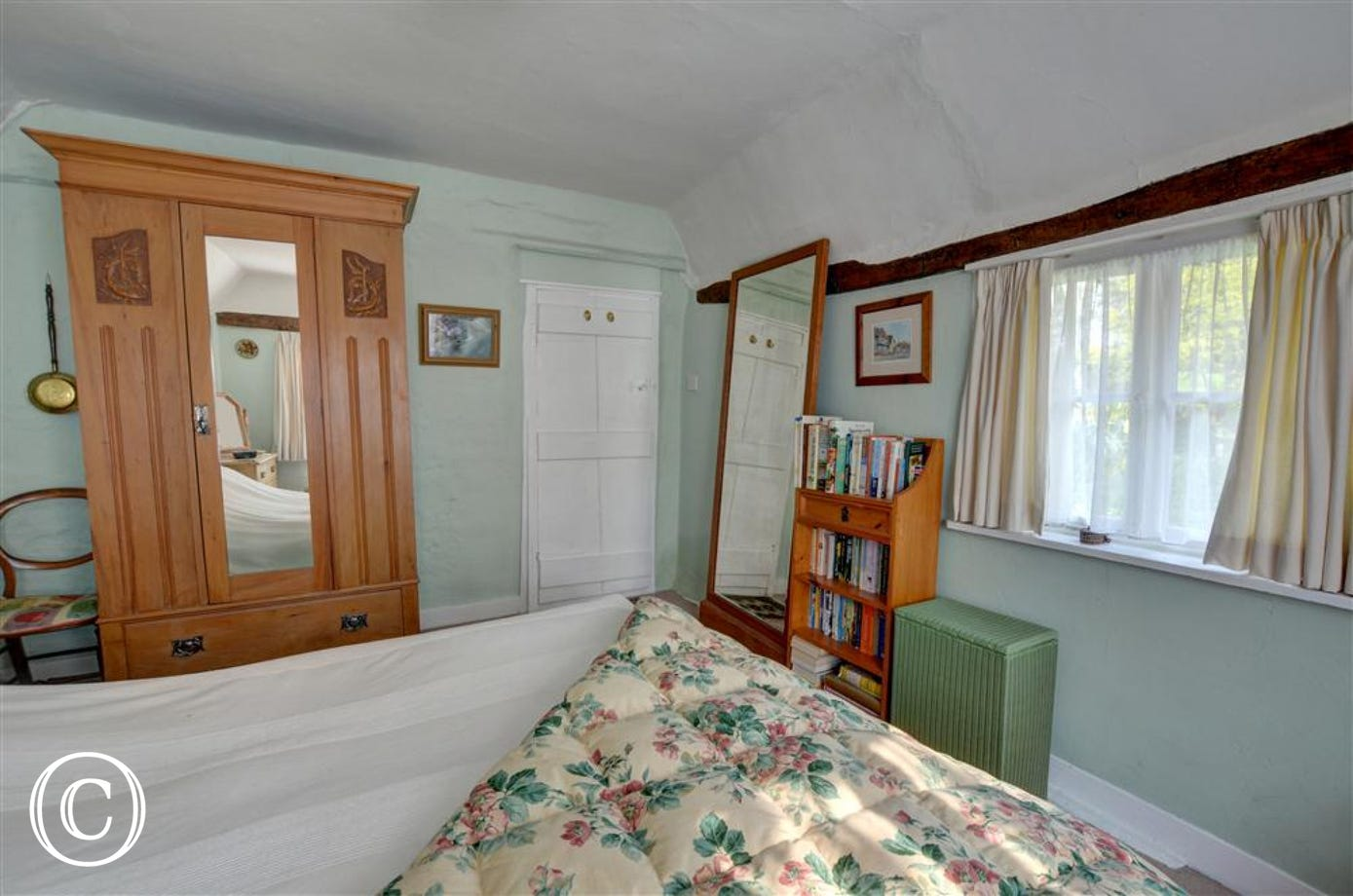 This main double bedroom has two windows with pretty views of the garden and this double bed to sink down into after a day in the generous garden.