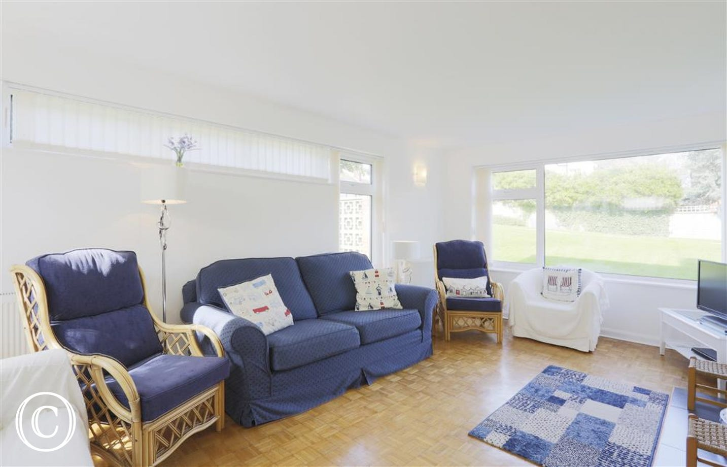 This sitting room with seaside blue finishing touches and soft furnishings makes for an ideal place to gather for a spot of television.