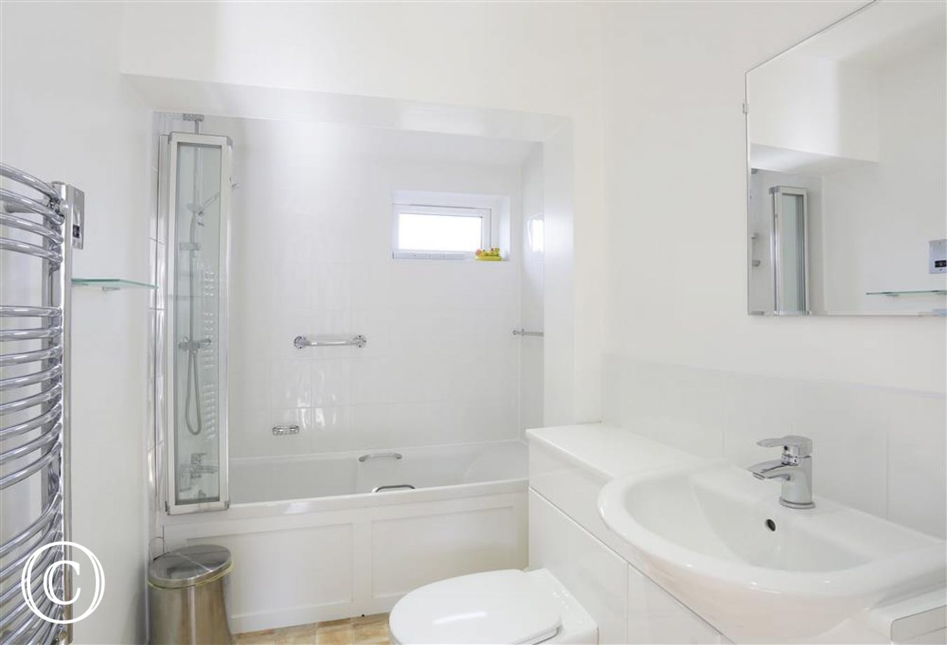 This fresh white bathroom, with bath, over bath shower, loo and basin will relax and refresh after a day on the beach.