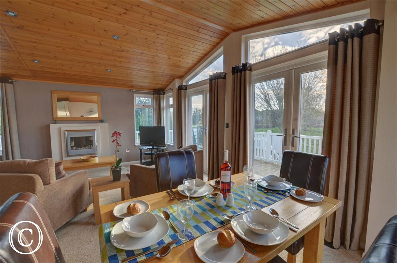 Gather at this dining table for 4 which has views over the decking area at the property and out over the lake.