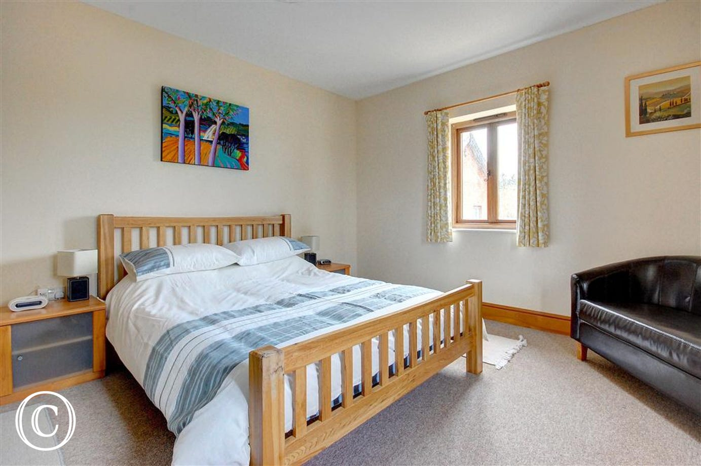 This main double bedroom has bedside tables and a tub sofa for two.