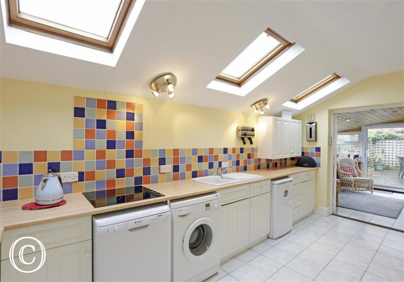This kitchen with colourful wall tiles is situated in the perfect spot for kitchen and conservatory.