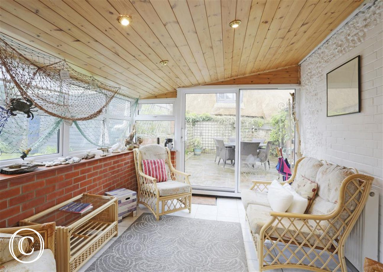 Enjoy relaxing in this conservatory with nautical theme and wicker chairs.