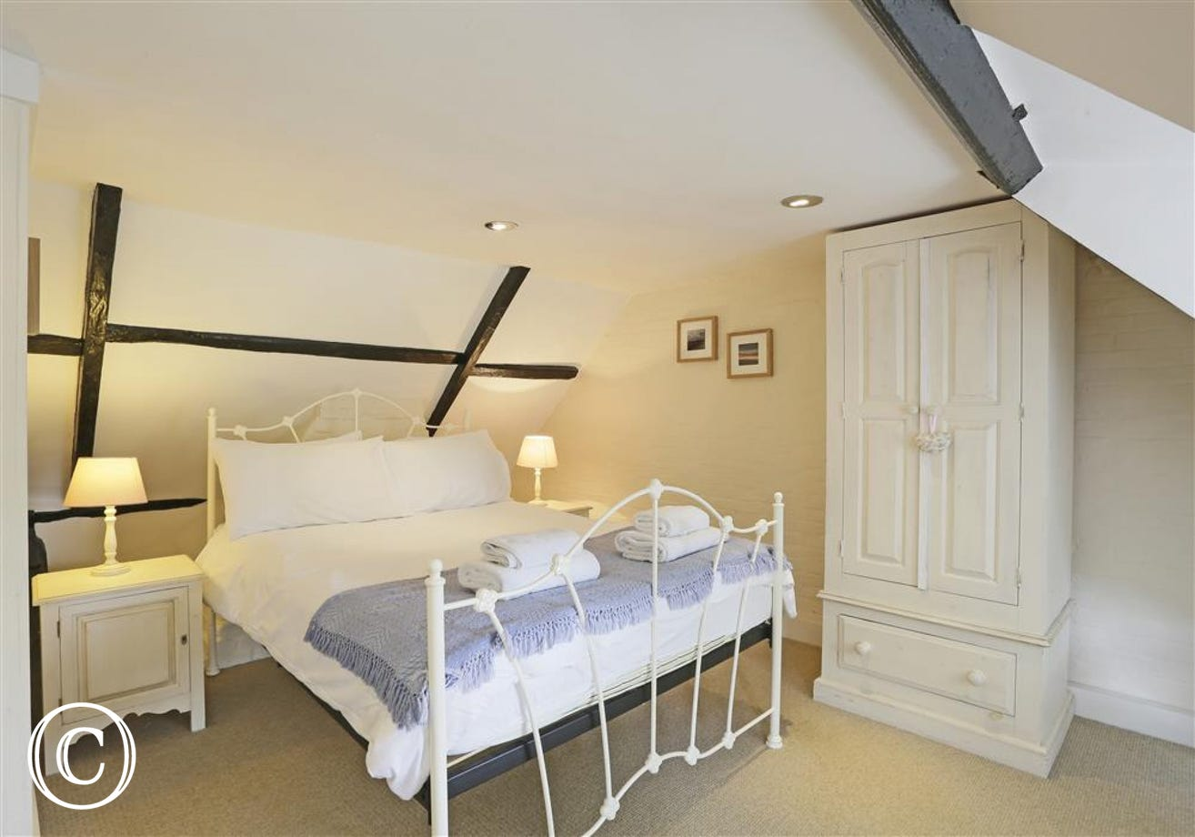 This master bedroom comes complete with a double bed and the room has character beams presenting the age of the cottage.
