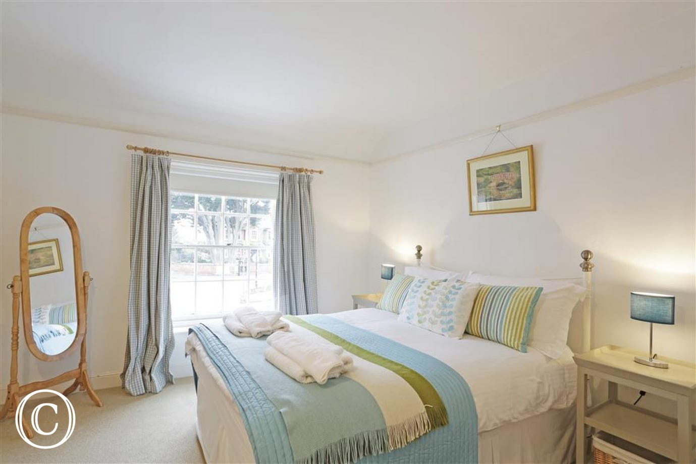 This main bedroom sleeps two people in this plush double bed with blue throw.