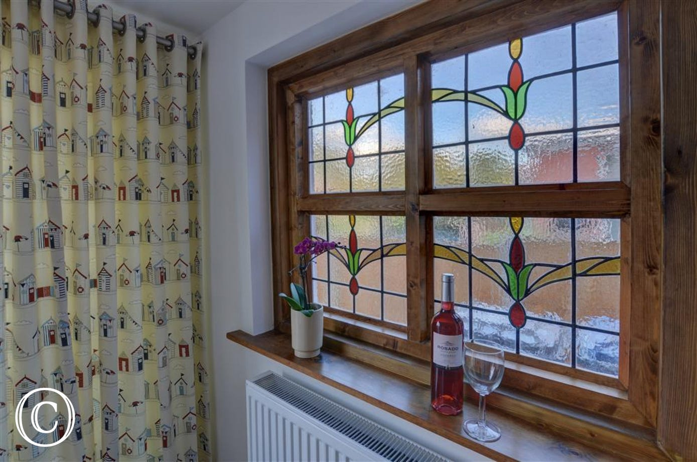 This pretty window with stained glass features in the dining area makes for a charming focal point whilst gathered at the table.