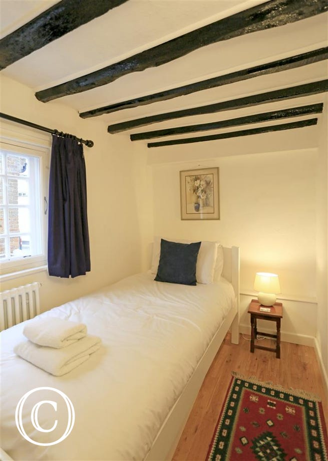 This single bedded room has neutral furnishings and is located on the ground floor at South West Cottage.