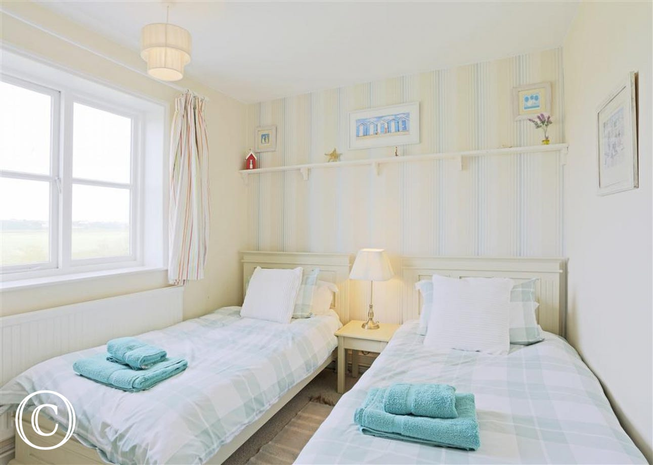 This twin room is the second one of three bedrooms providing comfort and luxury.