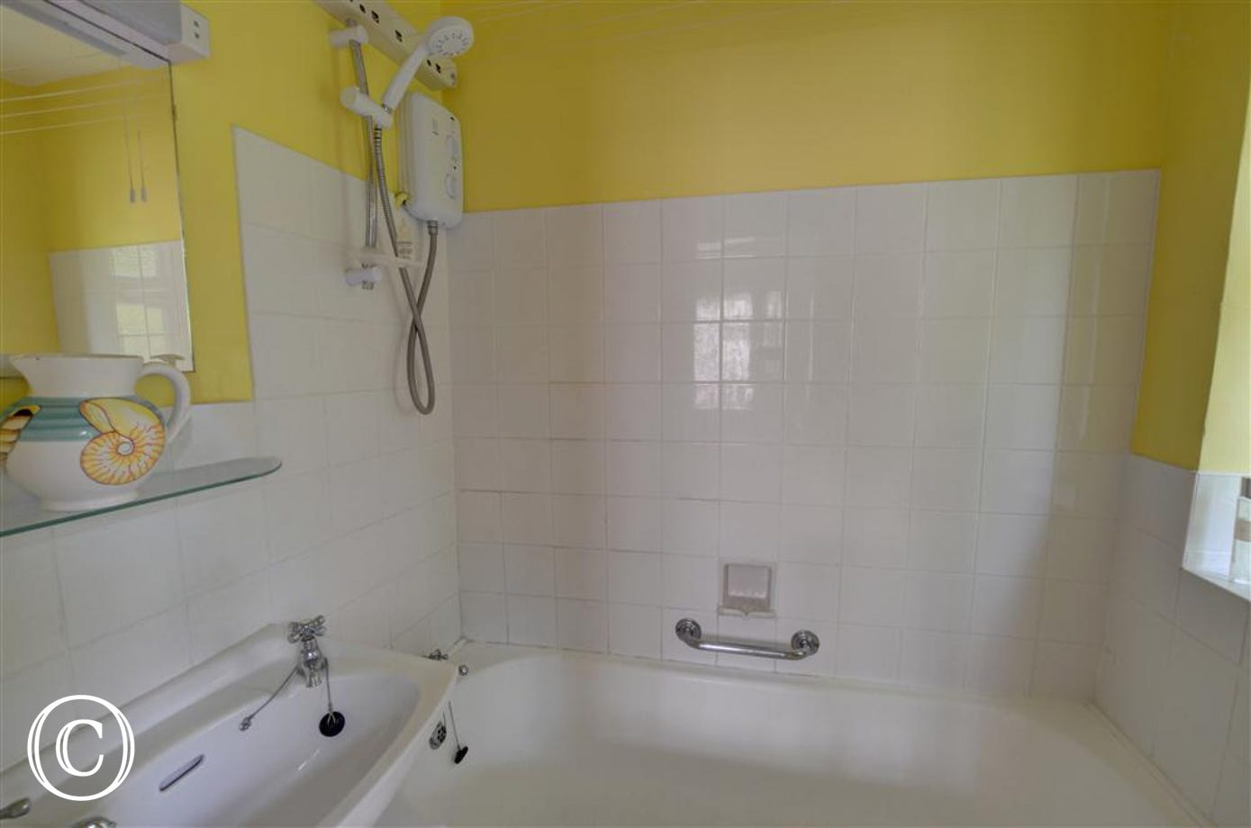This yellow walled bathroom with white tiles and suite will refresh after a day out to Bury St Edmunds.