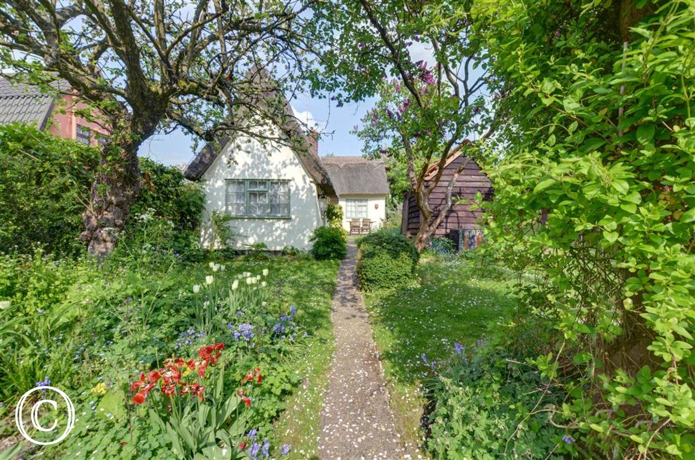 This pretty property dappled with sunlight through the blossom trees and foliage is a postcard property within the village of Denston.