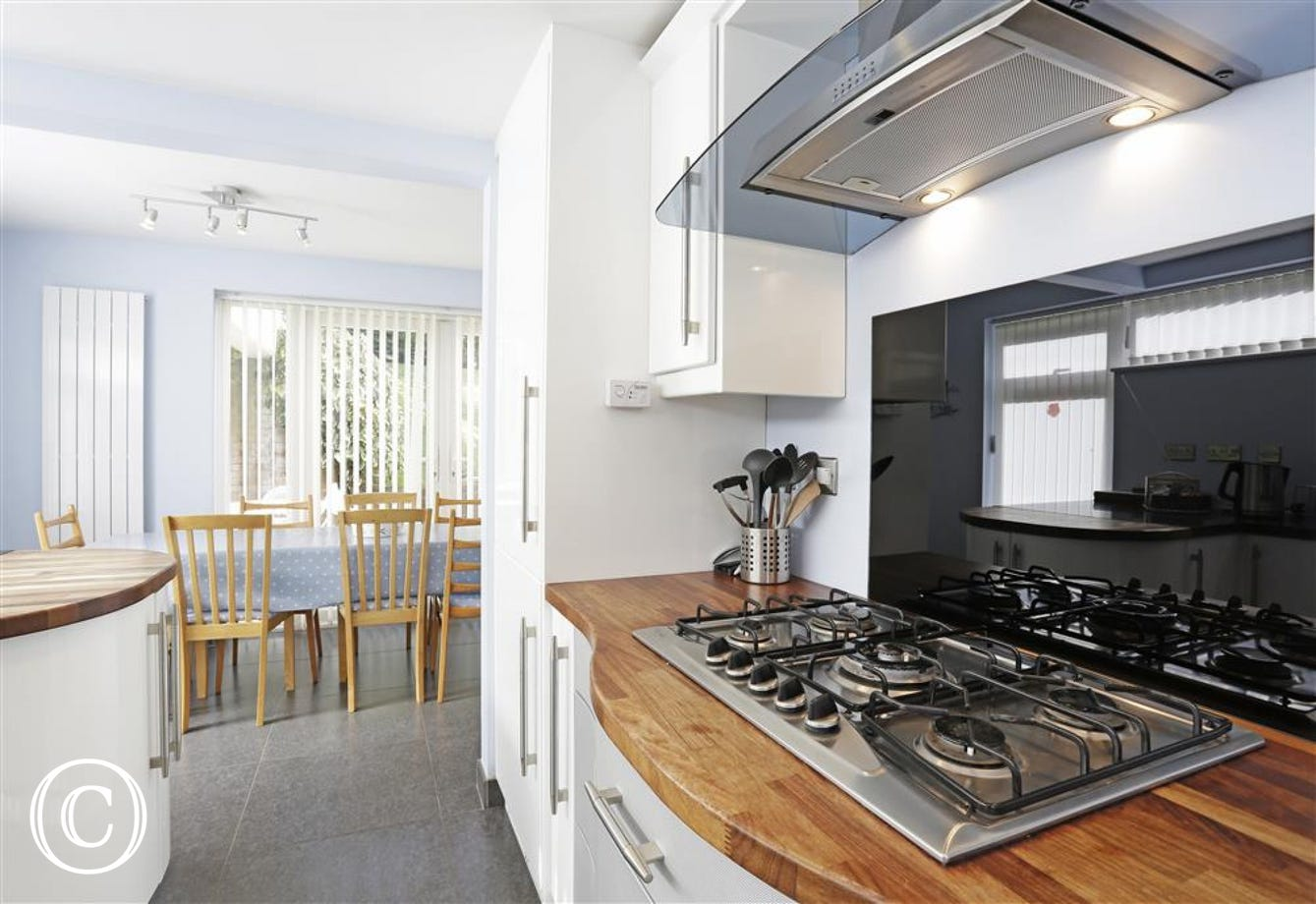This modern kitchen area is located close to the dining area and has access to the garden for that alfresco dining.