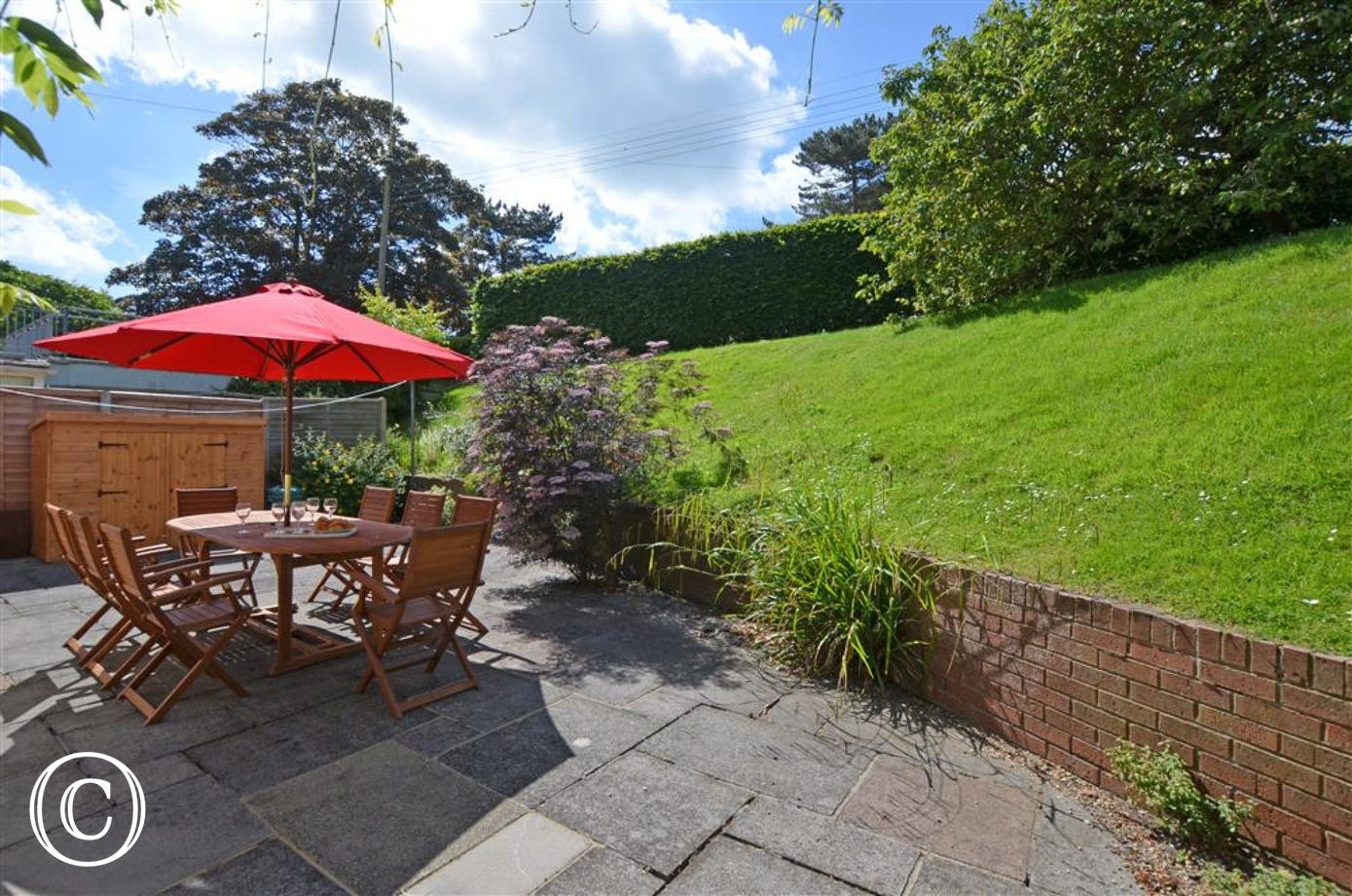 Enjoy all the flowers and the steeped lawns as you sit round this outside table chairs with red parasol.