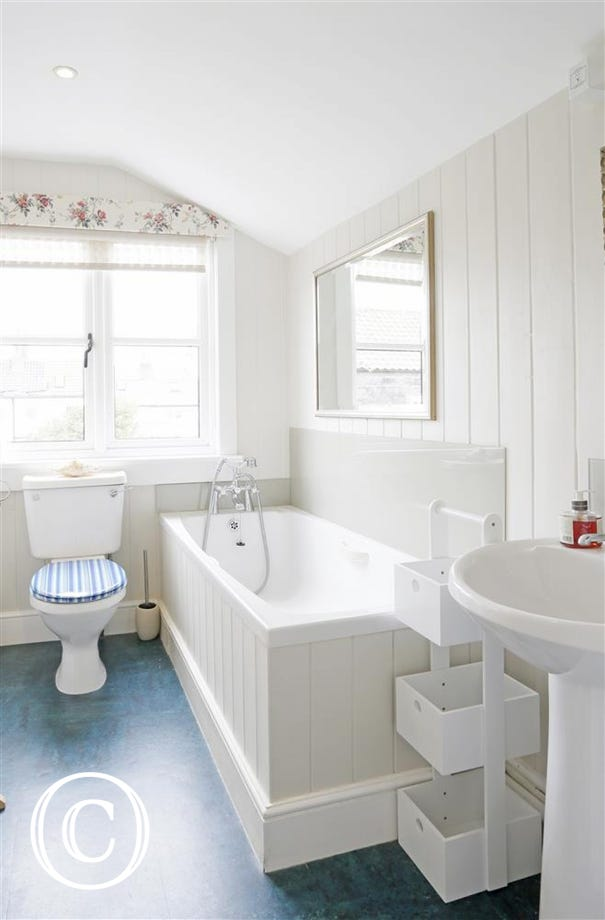 Enjoy relaxing in this fresh white day after a day on the beach in this en-suite bathroom.