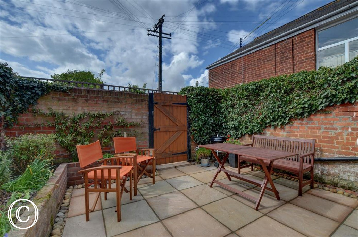 Enjoy this paved courtyard garden with rear access and plenty of seating to enjoy the sunshine.