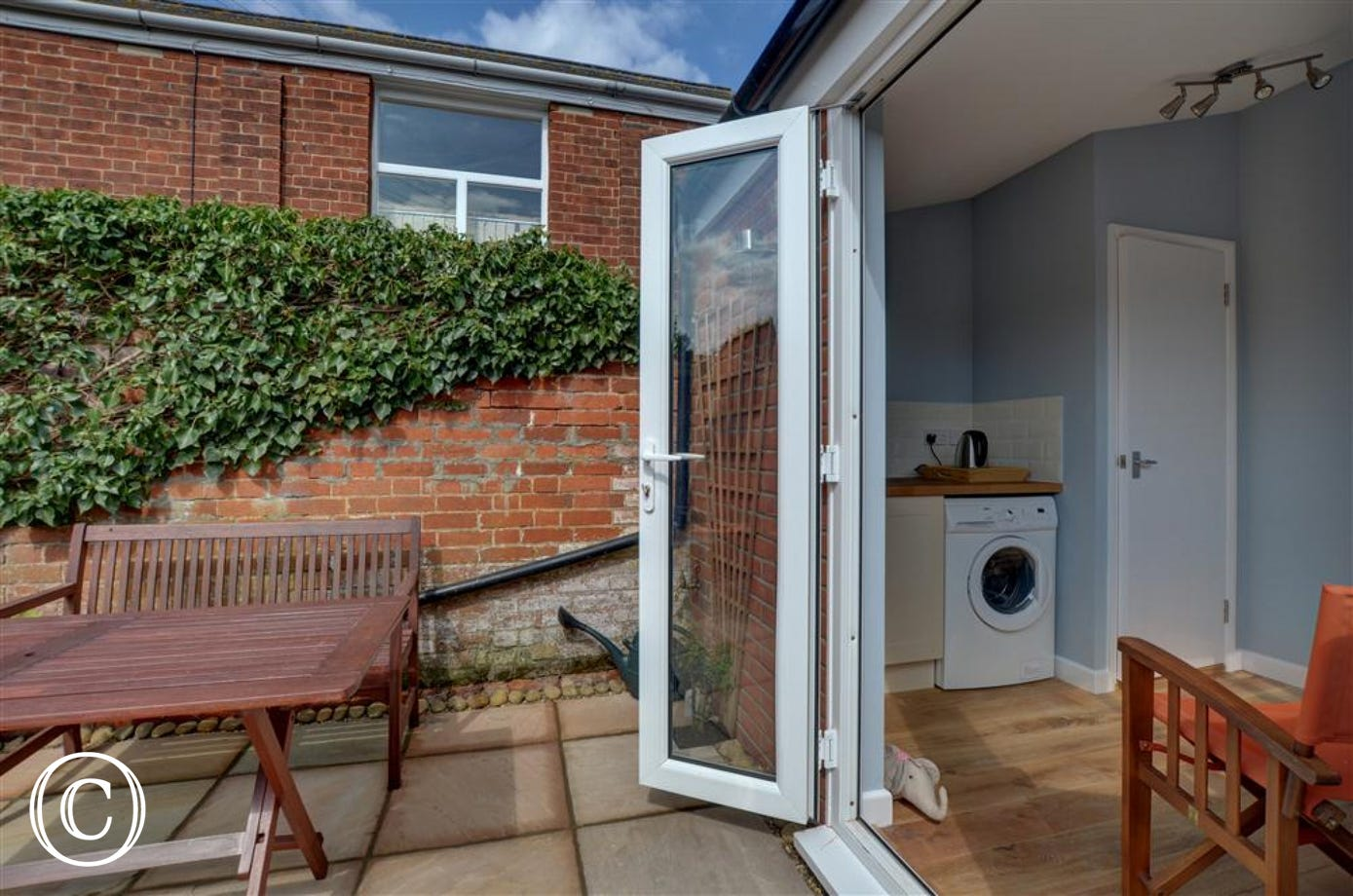 This garden room with sink kettle and washing machine makes a good area to prep for afternoon tea in the courtyard garden.