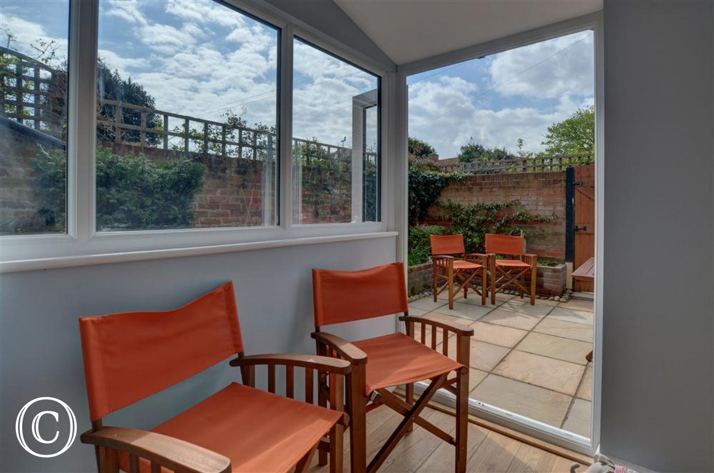 Enjoy sitting in this garden room on these orange director chairs and enjoying the warmth of the room of the view into the pretty courtyard garden.