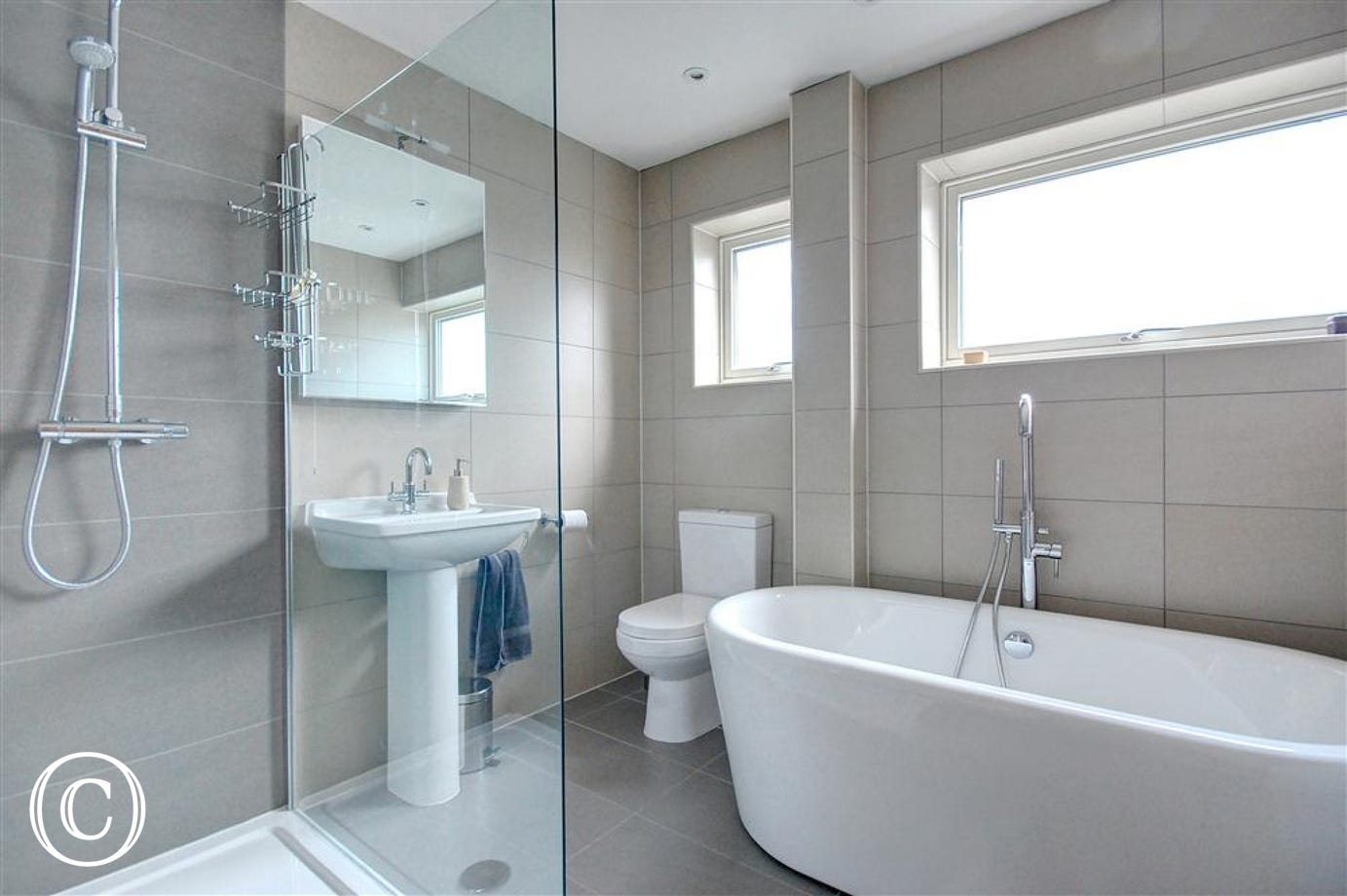 This modern fresh bathroom with roll top bath and biscuit coloured tiles is sure to help you relax.