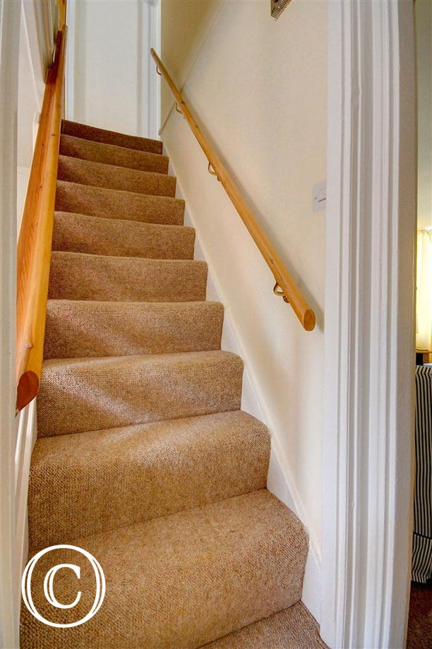 These stairs are carpeted and easy to use with a banister either side they go up to a small landing with a bedroom either side.