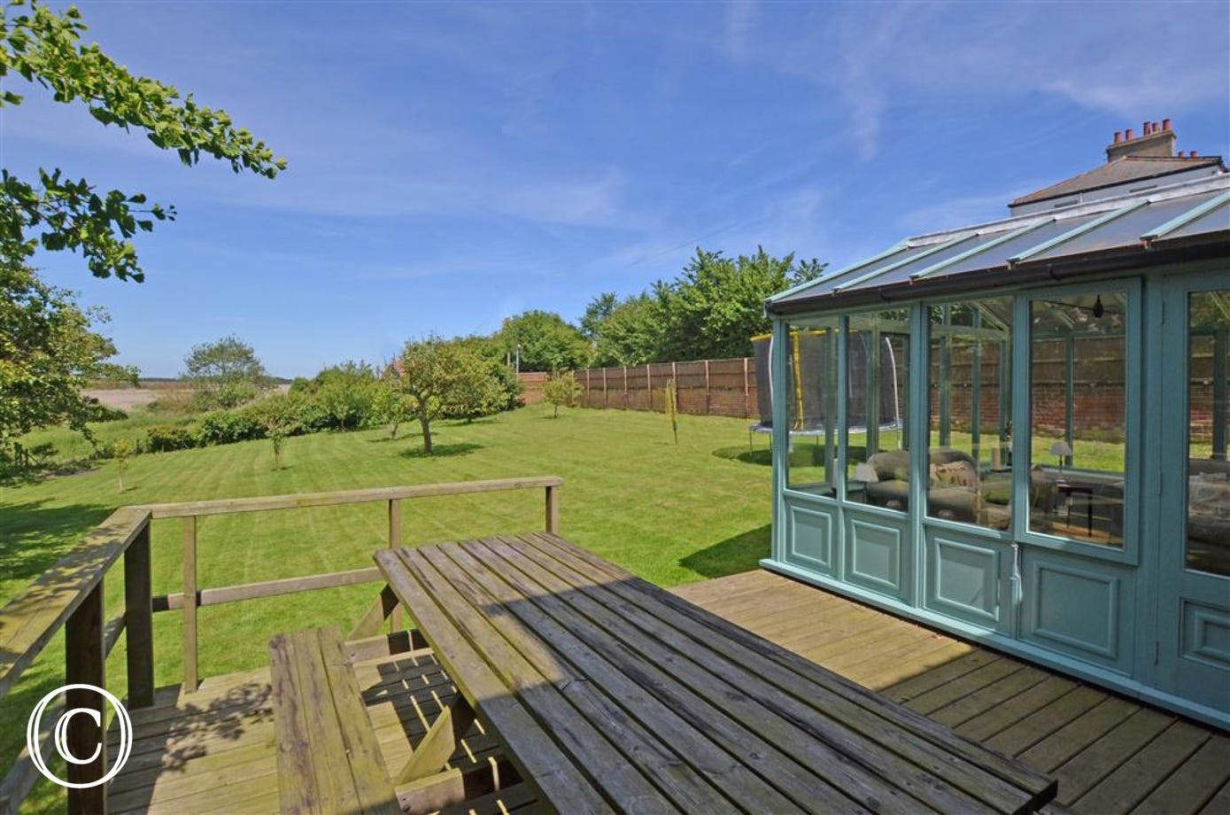 This decked area with picnic bench can be accessed from the garden or the conservatory.