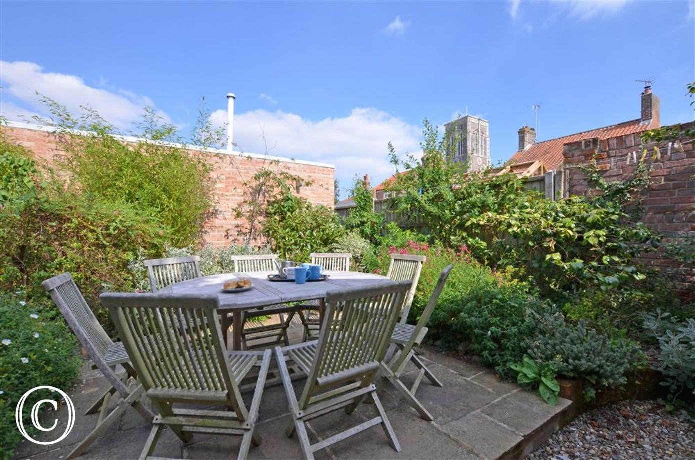 Enjoy the outside rear garden with its table and chairs.