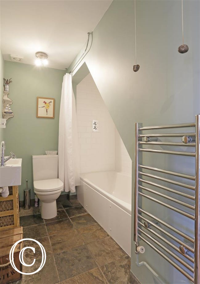 A well placed bathroom with added overbath shower facility.