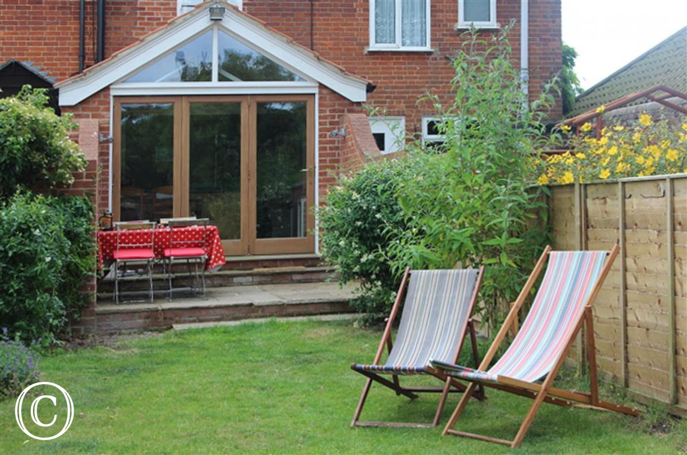 Enjoy this long garden with lawn and outside furniture like these stripy deck chairs.