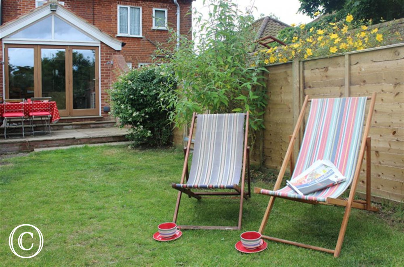 Sink down into these stripy deck chairs and enjoy a nice cup of tea in these bright red cups.