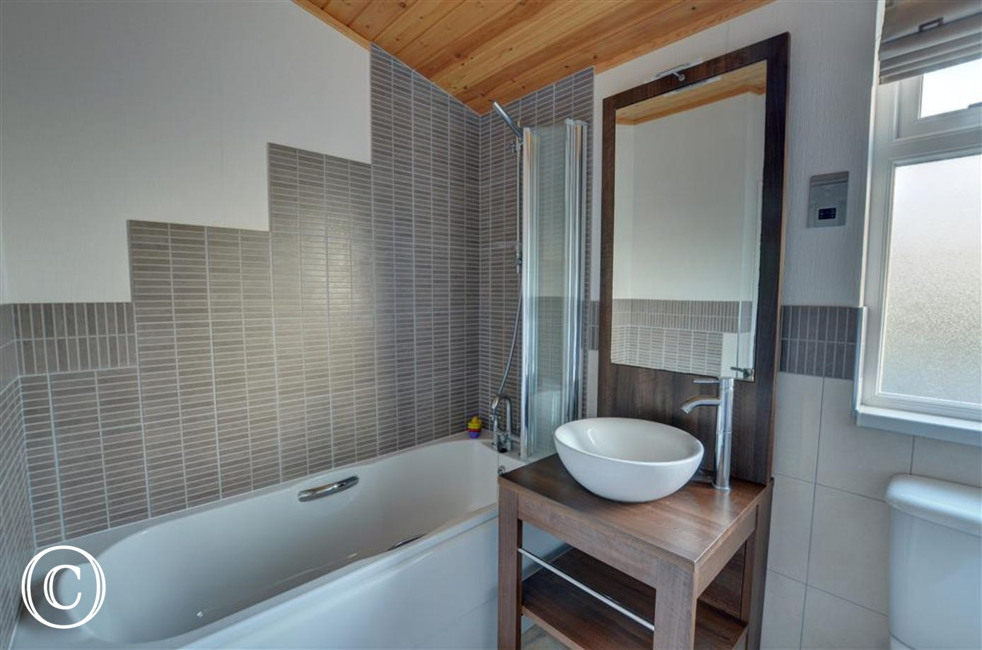 This main bathroom with modern tiling and over bath shower means you have a choice when it comes to revitalising ones self.