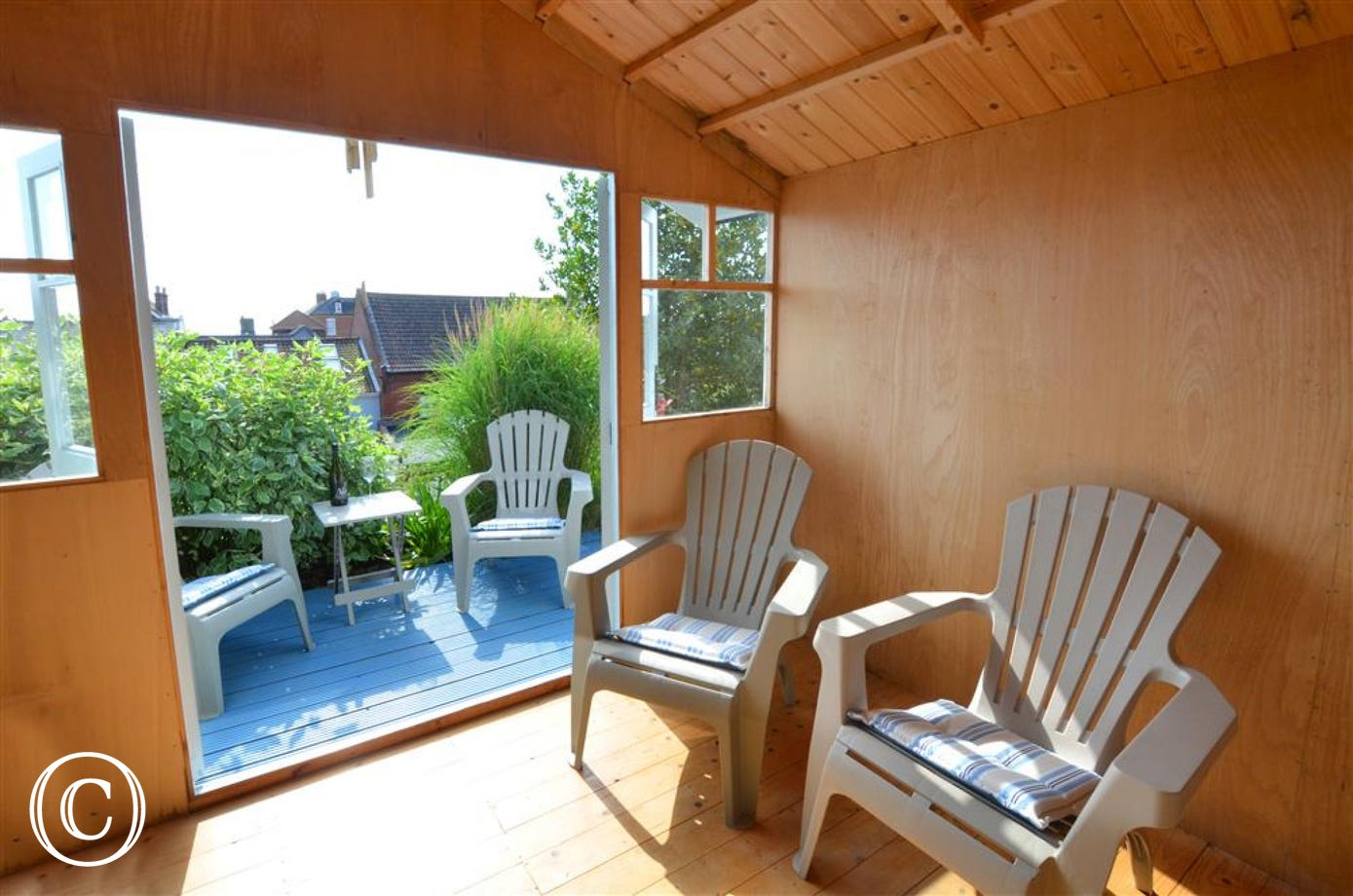 This warm amber wood is the inside of the Summer House, the doors are open in this image so you can get a feel for the decked area out front that one can sit out on to use as a viewing point.