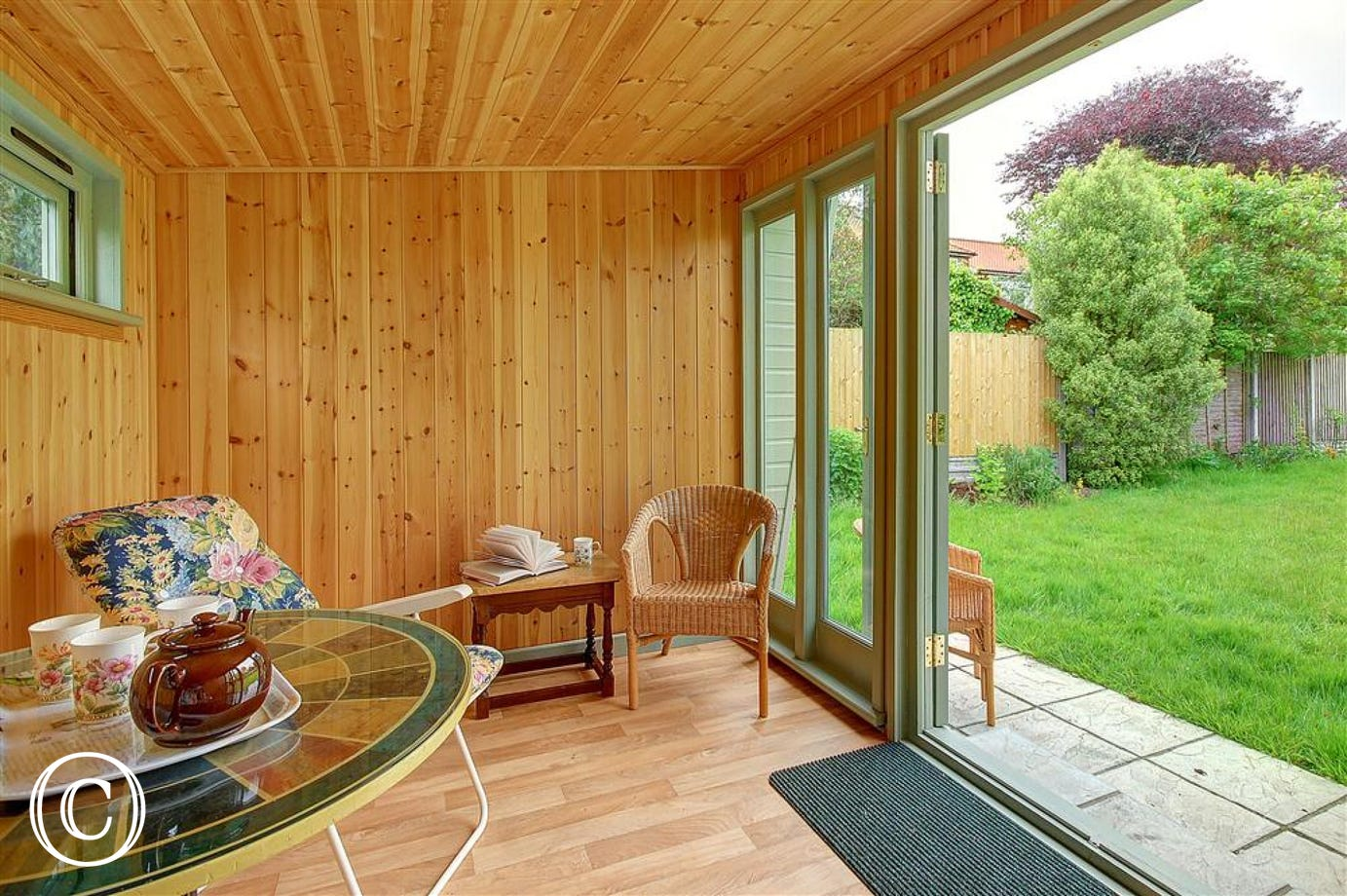 This welcoming summerhouse with warm wooden walls is great for enjoying a few alfresco meals and enjoying the garden.