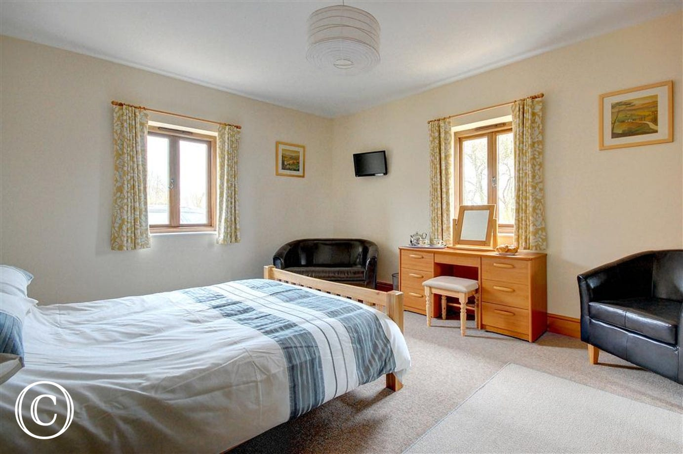 This bright double bedded room has all the luxuries one might expect with generous wardrobe dressing table television and tub sofa.
