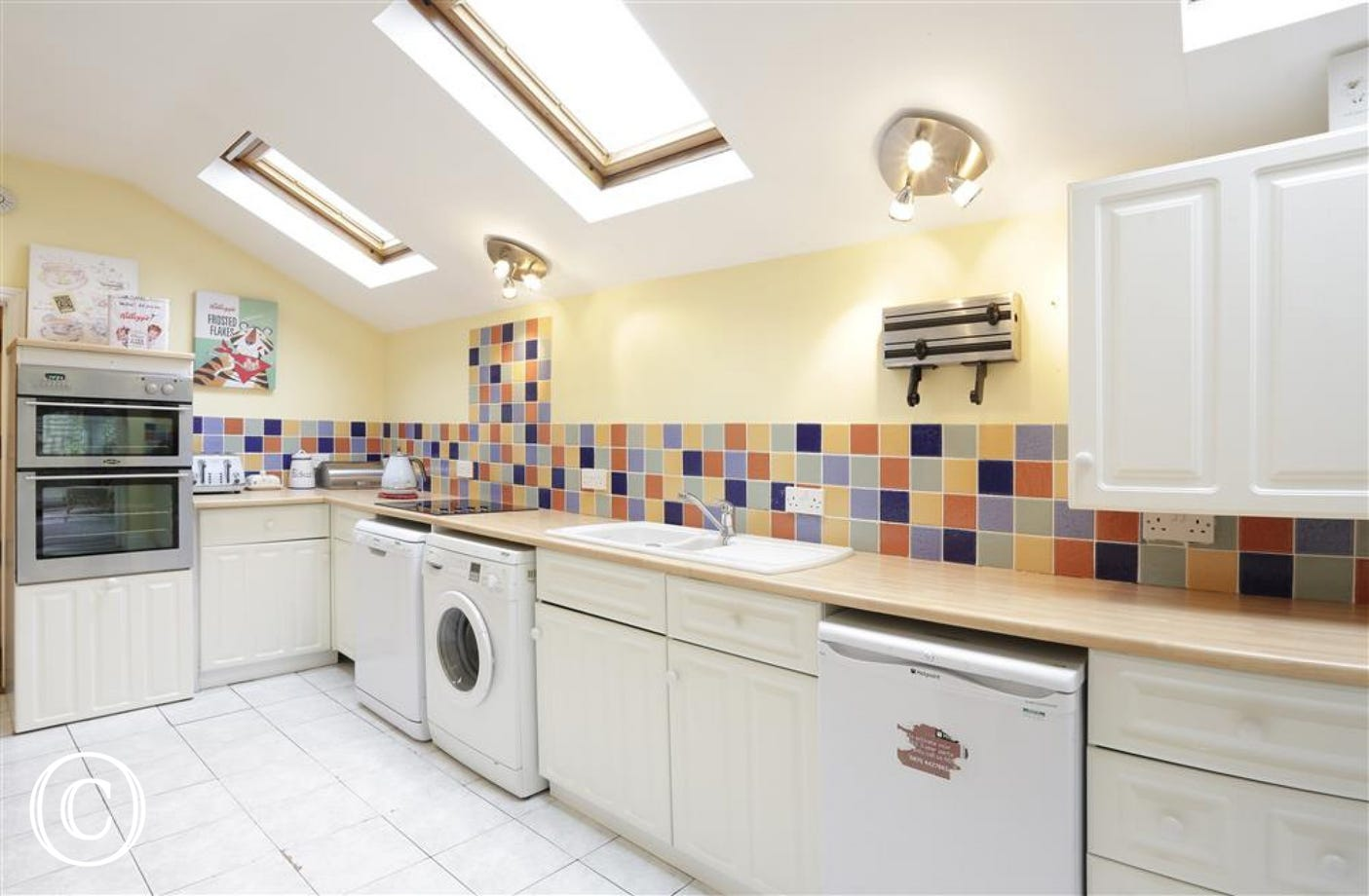 This kitchen with colourful wall tiles houses all the appliances one needs for a self-catering stay.