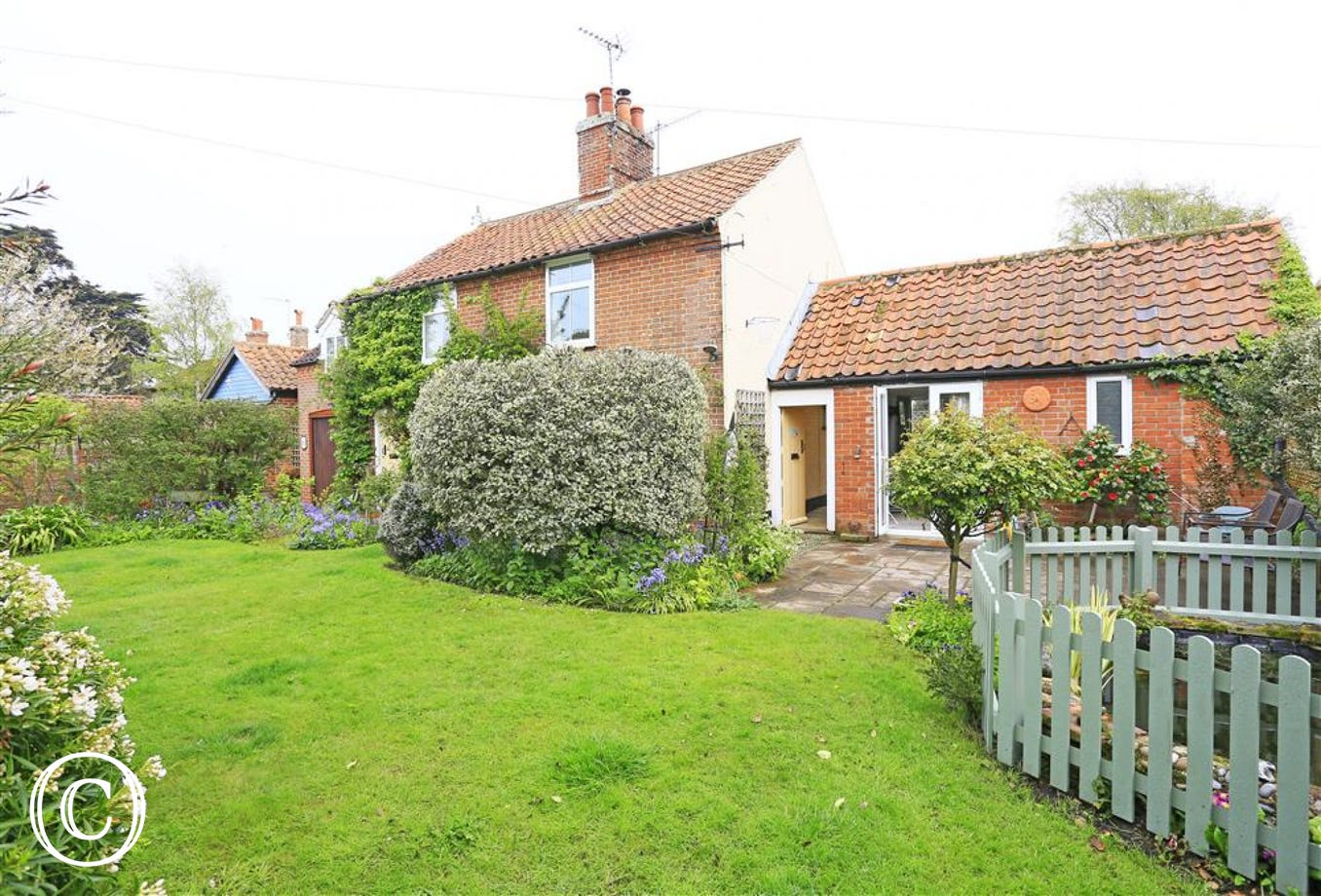 Enjoy the lawn and the mature flowers in this pretty Walberswick garden.