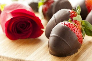 Strawberries dipped in chocolate next to red rose.
