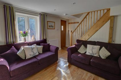 Enjoy this bright sitting room with plum coloured sofas and wood effect floors.