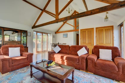 Spacious sitting room with comfortable seating and a beautiful vaulted ceiling