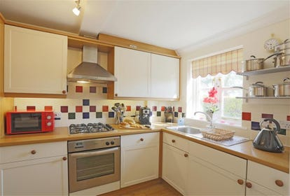 A modern cream coloured kitchen facility is packed full of essentials for making a meal to enjoy with all your guests.