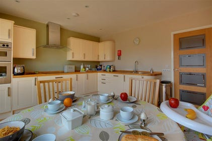 The square spacious kitchen is modern and fresh and has a smaller dining area for quick and easy meals.