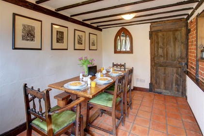 Gather in this medieval style dining area with red tiled floor and wooden dining table.