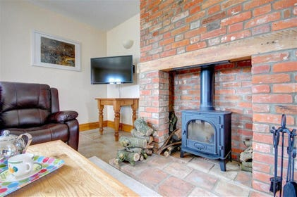 Enjoy toasting your toes by this wood burner in the sitting area.