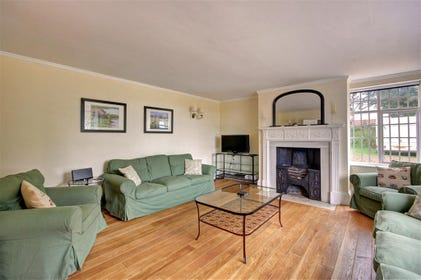 This wooden floored sitting room with sage coloured sofas is sure to make you feel welcome.